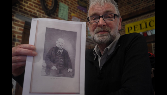 Adrian Tregerthen Thomas holding a photograph of his 3x grandfather.